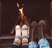 一对夫妇的浪漫腿在袜子的在wint的壁炉前面 免版税库存图片