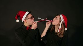 一对夫妇的画象在圣诞老人帽子的,他们在管子吹口哨在一个新年 影视素材