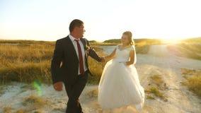 一对夫妇的配合在爱的 愉快的新娘和新郎奔跑在路 在爱的夫妇在夏天跑手在公园 股票录像