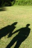 一对夫妇的阴影在草坪的 免版税库存照片