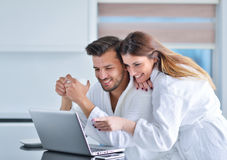 一对夫妇的画象在厨房和使用里膝上型计算机 库存照片