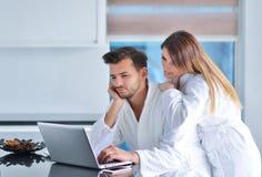 一对夫妇的画象在厨房和使用里膝上型计算机 库存图片