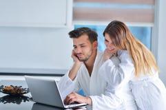 一对夫妇的画象在厨房和使用里膝上型计算机 免版税库存照片