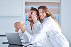一对夫妇的画象在厨房和使用里膝上型计算机 图库摄影