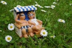 一对小矮小的夫妇在度假在一个绿色草甸的一张海滩睡椅说谎放松了有雏菊的 库存照片