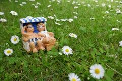 一对小矮小的夫妇在度假在一个绿色草甸的一张海滩睡椅说谎放松了有雏菊的 库存图片