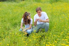 一对少年年轻夫妇获得乐趣在菊花的领域 免版税库存照片