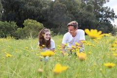 一对少年年轻夫妇获得乐趣在菊花的领域 免版税库存图片