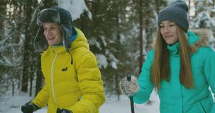 一对已婚夫妇的纵向 一个救生服和一名妇女的一个人一条蓝色连衫裤的在森林滑雪的冬天 股票视频