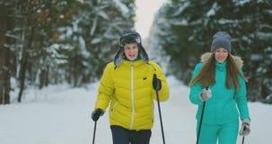 一对已婚夫妇的纵向 一个救生服和一名妇女的一个人一条蓝色连衫裤的在森林滑雪的冬天 影视素材