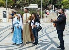 一对已婚夫妇-丈夫和怀孕的妻子耶稣`定期的立场衣裳的与attendantand吉他弹奏者在前面 图库摄影