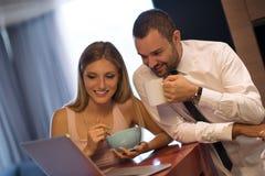 一对年轻夫妇为工作做准备并且使用膝上型计算机 免版税图库摄影