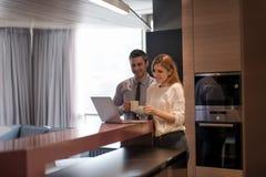 一对年轻夫妇为工作做准备并且使用膝上型计算机 免版税库存照片