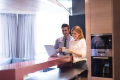 一对年轻夫妇为工作做准备并且使用膝上型计算机 库存图片