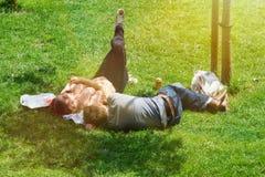 一对年轻夫妇享用休息和太阳在一个公园的草 库存图片