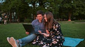 一对年轻夫妇在公园浏览互联网 影视素材