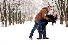 一对年轻夫妇在冬天公园走 图库摄影