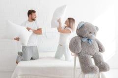 一对年轻夫妇在卧室打枕头 免版税图库摄影