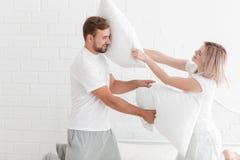 一对年轻夫妇在卧室打枕头 免版税库存照片