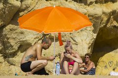 一对年轻夫妇在度假看他们的手机在阳光下在海滩的在Albuferia,葡萄牙 库存照片