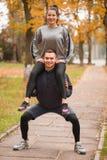 一对年轻夫妇在秋天公园训练 人拿着他肩膀和蹲下的女孩 图库摄影