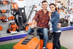 一对年轻夫妇坐割草机 库存图片