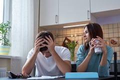 一对年轻夫妇坐在一张桌上在厨房里并且分析家庭预算 在家庭的金融危机 图库摄影