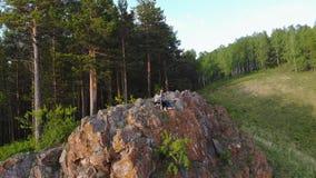 一对年轻夫妇坐在峭壁边缘并且享受美丽的景色 影视素材