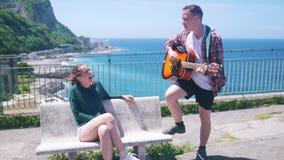 一对年轻夫妇坐在观察台的一条长凳度假胜地的背景的在海附近人使用 股票录像