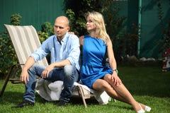 一对年轻夫妇坐deckchairs 库存照片