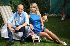 一对年轻夫妇坐deckchairs 库存图片
