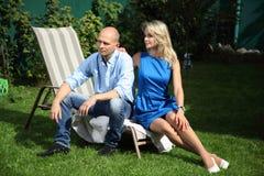 一对年轻夫妇坐deckchairs 图库摄影