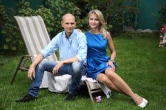 一对年轻夫妇坐deckchairs 免版税库存照片