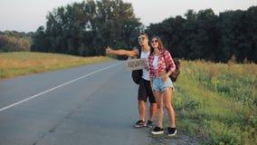 一对年轻夫妇搭车在路的身分 男人和妇女停止在高速公路的汽车有任何地方标志的 影视素材