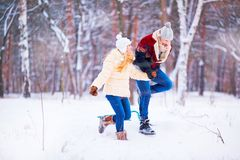 一对年轻夫妇是在雪的连续乐趣在冬天公园 库存图片