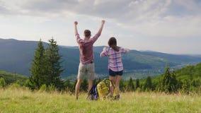 一对年轻夫妇是愉快来到山的一个休息处 触击他们的手,拥抱 冲入框架 股票录像