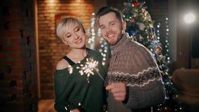 一对年轻夫妇是愉快的亲吻拿着闪烁发光物的在圣诞节 新年好 股票视频
