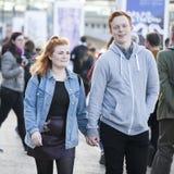 一对年轻夫妇步行沿着向下握手的街道 免版税图库摄影