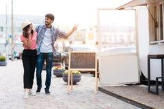 一对年轻夫妇步行沿着向下街道到一个流动吃饭的客人 他们要发出订单 库存照片