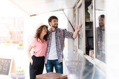 一对年轻夫妇步行沿着向下街道到一个流动吃饭的客人 他们要发出订单 免版税库存照片
