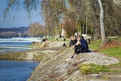 一对年轻夫妇由河坐并且敬佩看法在一温暖的好日子 放松由河 假日、假期、爱和人们 库存照片