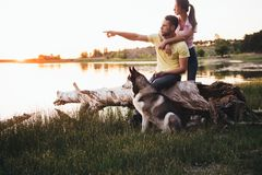 一对年轻夫妇由湖坐在与一条多壳的品种狗的日落 免版税图库摄影
