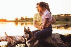 一对年轻夫妇由湖坐在与一条多壳的品种狗的日落 免版税库存图片