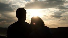 一对年轻夫妇的剪影在日落的 妇女在她的男朋友的肩膀上把她的头放 股票视频