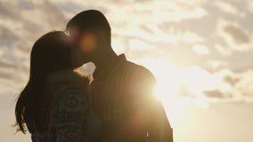 一对年轻夫妇的剪影在爱的在天空和太阳背景,看彼此 股票录像