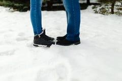 一对年轻夫妇的特写镜头脚在温暖的冬天穿上鞋子在雪的身分 一个男人和一名妇女的腿冬天起动的站立  免版税库存照片