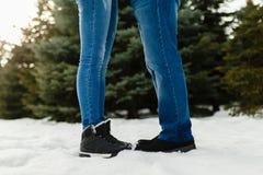 一对年轻夫妇的特写镜头脚在温暖的冬天穿上鞋子在雪的身分 一个男人和一名妇女的腿冬天起动的站立  免版税库存图片