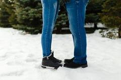 一对年轻夫妇的特写镜头脚在温暖的冬天穿上鞋子在雪的身分 一个男人和一名妇女的腿冬天起动的站立  库存照片