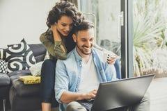 一对年轻夫妇的画象使用室内膝上型计算机的在家 库存照片