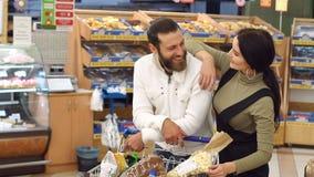 一对年轻夫妇的画象在超级市场,当选择新鲜面包时 股票录像